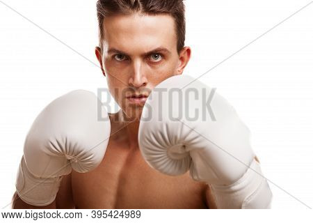 Close Up Of A Fierce Male Boxer Holding Up His Fists In Boxing Gloves. Professional Fighter In Fight