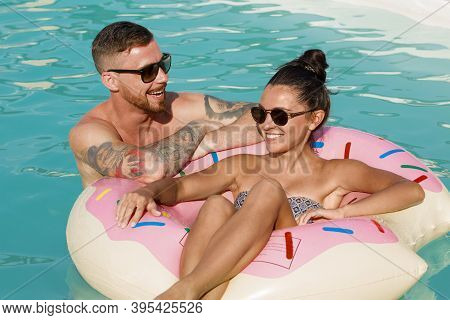 Happy Couple Talking While Swimming On Inflatable Donut At The Pool. Beautiful Woman Sitting On Pool