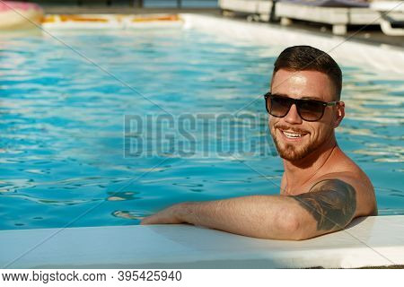 Cheerful Handsome Bearded Man With Tattoos Smiling To The Camera, While Relaxing In The Swimming Poo