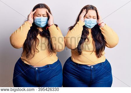 Young plus size twins wearing medical mask with hand on head for pain in head because stress. suffering migraine.