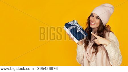 Happy Young Woman Smiling Pointing Finger Holding Blue Gift Box In Hand. A Gift To Your Beloved Man.
