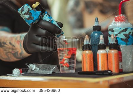 Red Tattoo Ink Spreading In Glass Of Water On The Foreground, Tattoo Artist Working With A Customer,