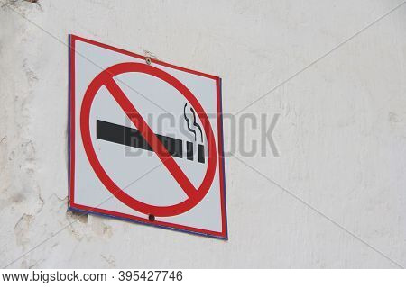 No Smoking Sign On White Wall, Concept Of Health Care, Smoking Cessation. Smoking Cigarette In A Cro