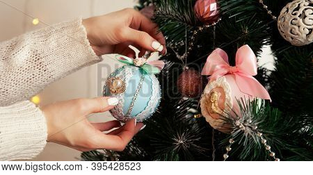 Close-up Of Female Hands Hang The Ball On The Tree. Christmas Decoration, Toys Hanging On The Tree,
