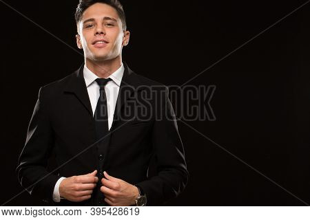 Portrait Of A Handsome Young Man Wearing Elegant Black Suit And Tie Posing Confidently On Black Back