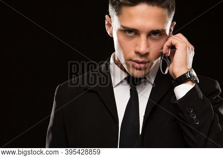 Close Up Of A Handsome Young Suited Secret Service Agent Looking To The Camera Fiercely Talking On H