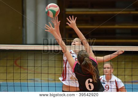 KAPOSVAR, HUNGARY - OCTOBER 14: Zsofia Harmath (C) in action at the Hungarian I. League volleyball game Kaposvar (white) vs Nyiregyhaza (black), October 14, 2012 in Kaposvar, Hungary.