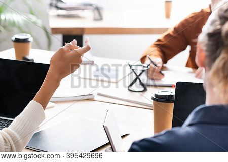Cropped Of African American Woman Gesturing While Sitting At Workplace With Blurred Co-worker Writin