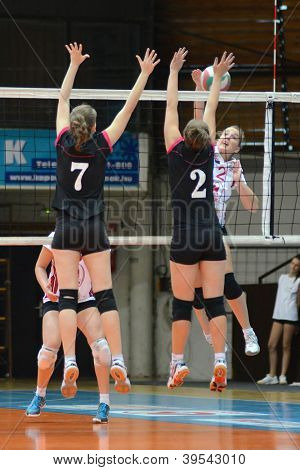 KAPOSVAR, HUNGARY - OCTOBER 14: Zsanett Pinter (in white) in action at the Hungarian I. League volleyball game Kaposvar (white) vs Nyiregyhaza (black), October 14, 2012 in Kaposvar, Hungary.