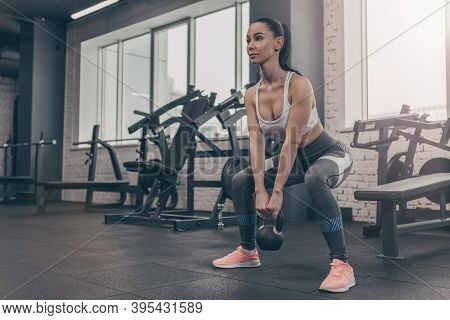 Low Angle Shot Of A Sexy Female Athlete Exercising With Kettlebell At The Gym. Beautiful Woman Doing