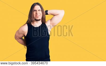 Young adult man with long hair wearing goth style with black clothes suffering of neck ache injury, touching neck with hand, muscular pain