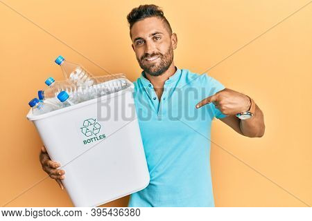 Handsome man with beard holding recycling wastebasket with plastic bottles pointing finger to one self smiling happy and proud