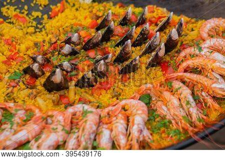 Close Up: Cooked Yellow Paella With Shrimp, Mussel, Rice, Saffron In Huge Paella Pan At Summer Outdo