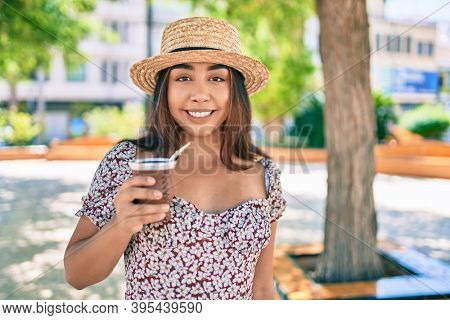 Young latin woman on vacation drinking cup of mate tea walking at street of city.