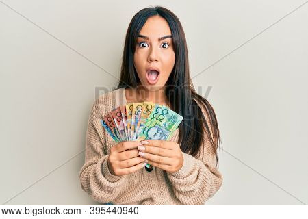 Young beautiful hispanic girl holding australian dollars afraid and shocked with surprise and amazed expression, fear and excited face.