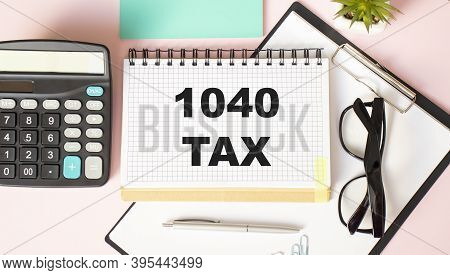The Tablet With Text 1040-tax On Business Charts And Calculator