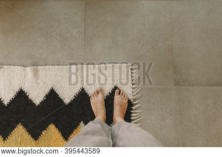 Woman Barefoot Standing On Modern Rug In Comfortable Stylish Home, Top View. Feet On Cozy Woolen Rug