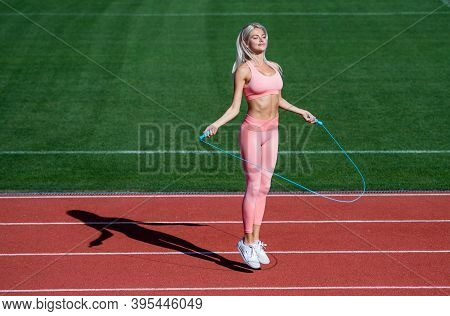 Jumping Higher. Athletic Lady Use Jumping-rope On Stadium. Female Athlete Do Jumping Sport Workout.