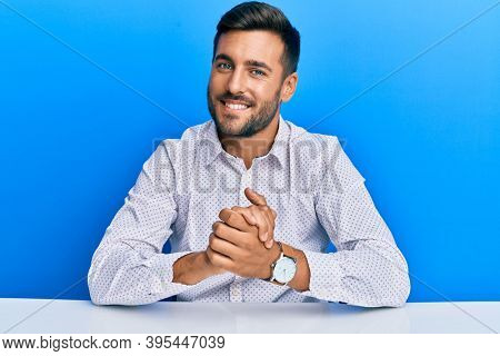 Handsome hispanic man wearing business clothes sitting on the table with hands together and crossed fingers smiling relaxed and cheerful. success and optimistic