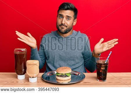 Handsome hispanic man eating a tasty classic burger and soda clueless and confused with open arms, no idea and doubtful face.