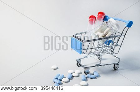 Medicine Concept. Various Capsules, Pills And Medicines In A Shopping Cart On A Gray Background With