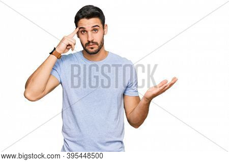 Young hispanic man wearing casual clothes confused and annoyed with open palm showing copy space and pointing finger to forehead. think about it.