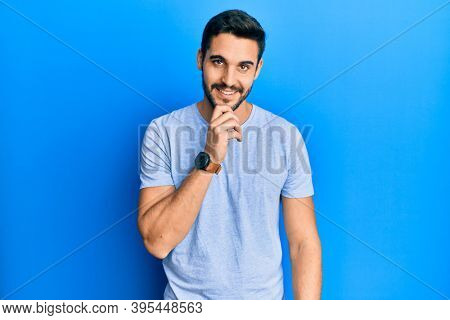 Young hispanic man wearing casual clothes smiling looking confident at the camera with crossed arms and hand on chin. thinking positive.
