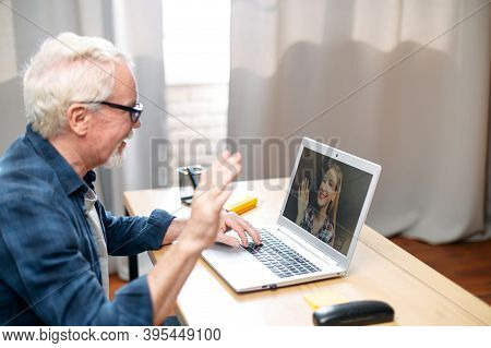 A Gray-haired Grandpa Talking With A Granddaughter Via Video Call On Laptop While Sitting At Home