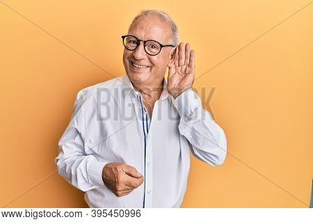 Senior caucasian man wearing casual clothes and glasses smiling with hand over ear listening and hearing to rumor or gossip. deafness concept.
