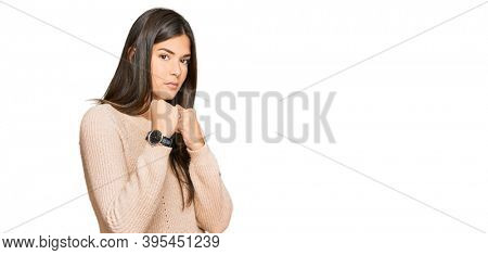 Young brunette woman wearing casual winter sweater ready to fight with fist defense gesture, angry and upset face, afraid of problem
