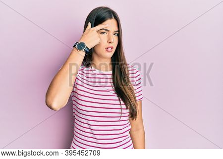 Young brunette woman wearing casual clothes over pink background pointing unhappy to pimple on forehead, ugly infection of blackhead. acne and skin problem
