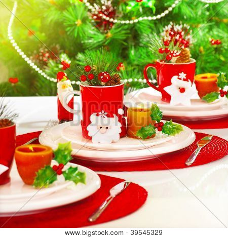 Photo of beautiful Christmas table setting, New Year banquet, adorned evergreen tree, warm yellow sun light in dinning room, luxury porcelain dishware with red festive cup for tea, holiday decoration