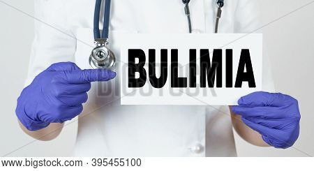 Medicine And Health Concept. The Doctor Points His Finger At A Sign That Says - Bulimia