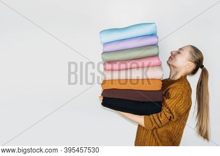 Woman Holding Stack Of Pastel Natural Color Fabrics On White Background. Fabrics And Clothing Arrang