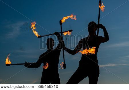 Rise To The Challenge. Sexy Couple Manipulate Burning Rods. Dark Silhouettes Twirl Fire Rods On Idyl