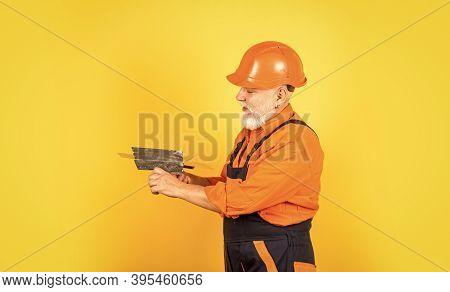He Needs Little Break. Plasterer In Working Uniform Plastering. Man With Spatula. Process Of Applyin
