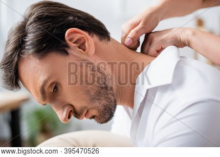 Close Up View Of Masseuse Massaging Neck Of Bearded Businessman On Blurred