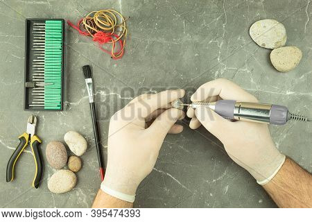 The Hands Of A Man Engrave The Stone With The Help Of An Engraver. Professional Engraving On Stones