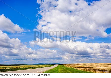 Straight Empty Road On Prairie Under Blue Sky And Low Clouds, In Alberta, Canada.