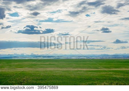 Prairie Landscape With Mountains In Distance Under Low Clouds, In Alberta, Canada.
