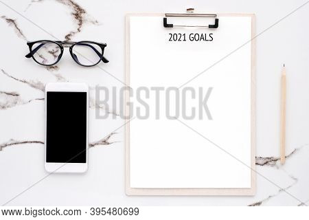2021 Goals On Blank Note Paper With Copy Space For Text And Smartphone With Blank Screen On White Ma