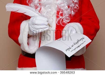 Santa Claus holding a quill pen whilst checking the naughty or nice list.