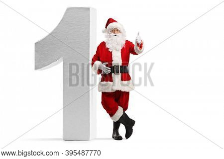 Full length portrait of santa claus leaning on number one and showing thumbs up isolated on white background