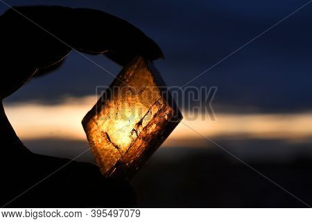 A Silhouette Image Of A Hand Holding A Piece Of Honey Calcite Crystal Against A Golden Sunset Sky.
