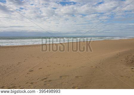 Footprints In Sand On Beach Leading Down To Ocean Waves
