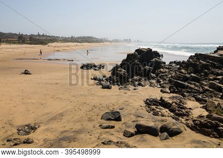 Black Rocks On Beach At Low Tide With Fishermen In Background