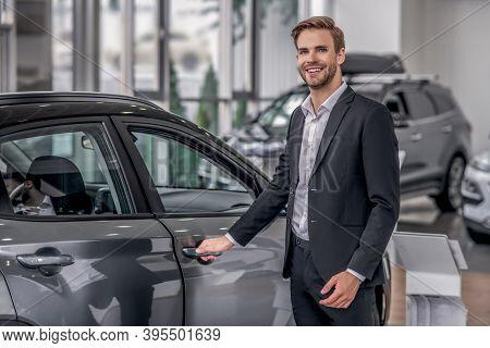 Smilng Male Opening Car Door In The Showroom
