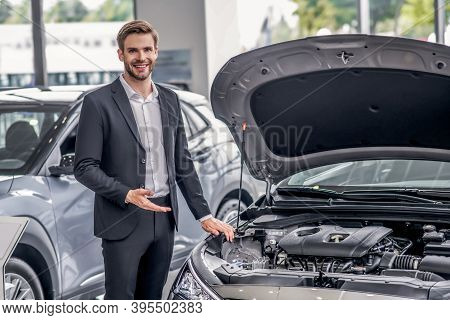 Smiling Brown-haired Male Pointing At Open Car Hood