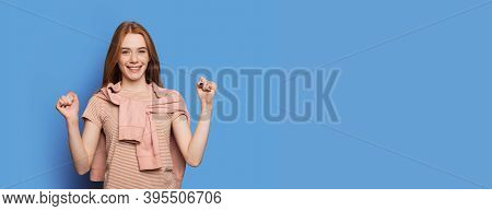 Freckled Woman With Red Hair Is Gesturing The Yes Sign While Advertising Something On A Blue Studio