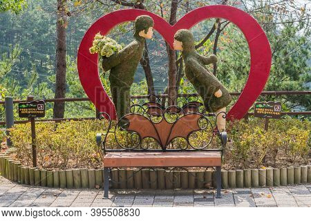 Cheongyang-gun, South Korea; October 2, 2020: Statue Of Couple About To Kiss In Front Of Red Heart A